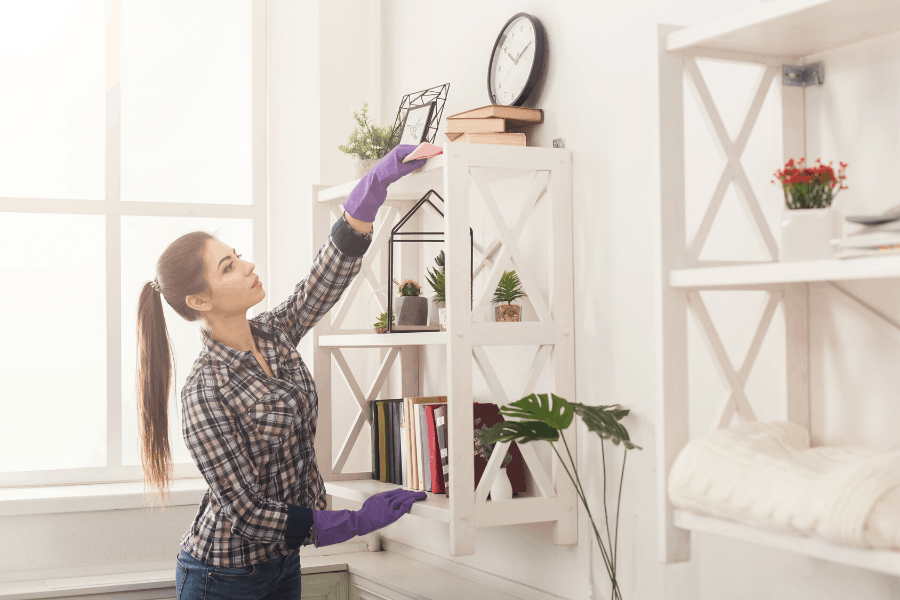 woman dusting shelves